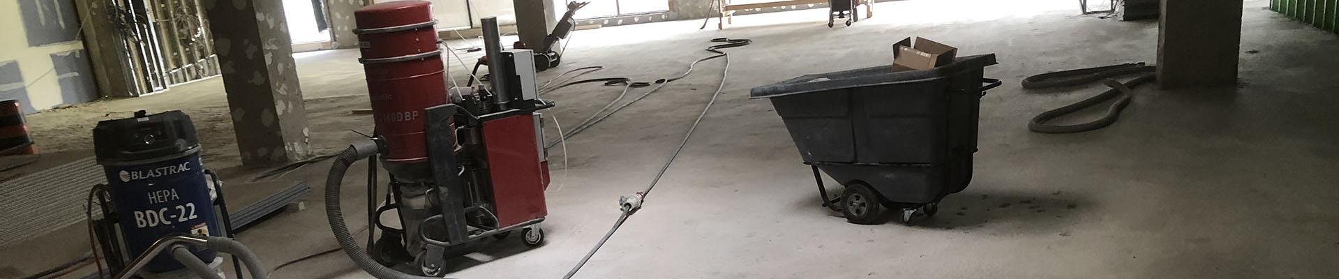 Concrete floor unfinished with vacuums and tools showing