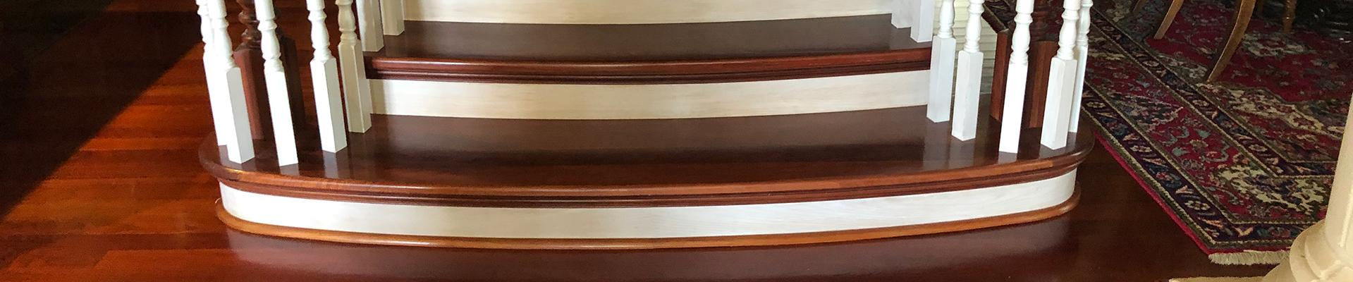 Closeup of wooden stairs with white trim